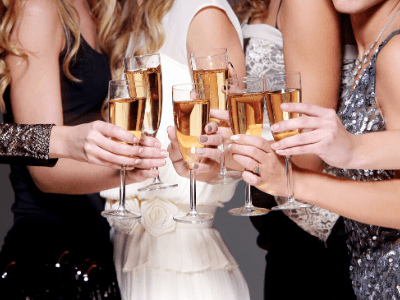 A close up of a group of women holding champagne flutes and champagne