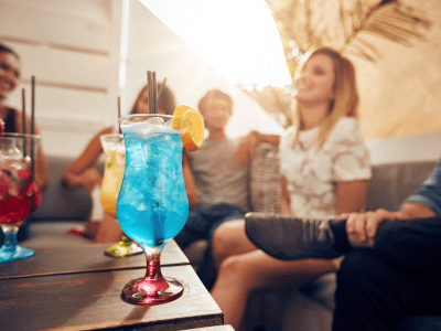 A group of friends enjoying colourful cocktails whilst relaxing on lounges
