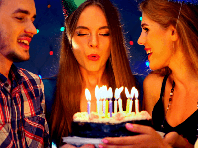 A woman blowing out the candles of a birthday cake wih her friends