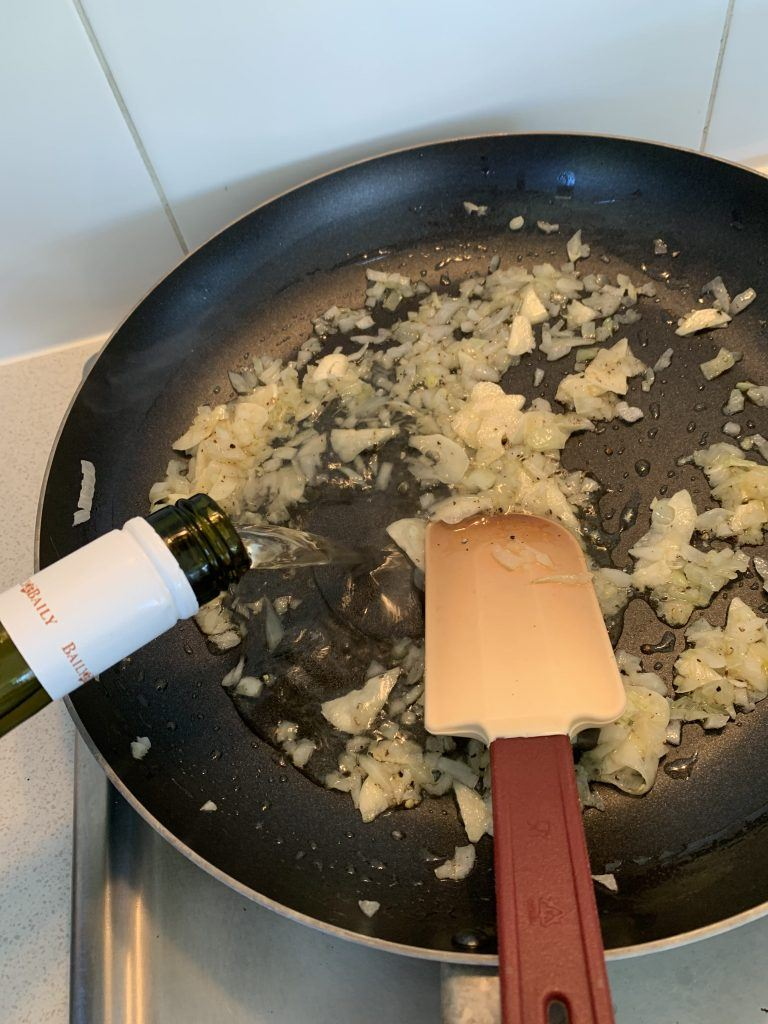 White wine being poured into a pan with garlic and onion